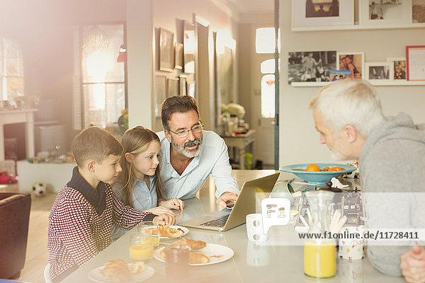 Männliche schwule Eltern und Kinder mit Laptop an der Frühstücksküche