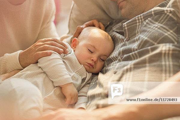 Müde schlafender Baby-Sohn schläft mit Vater