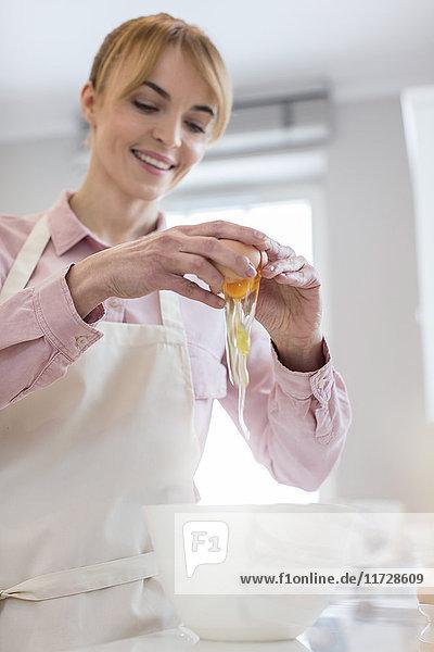 Lächelnde Frau beim Backen  knackendes Ei über der Schüssel in der Küche