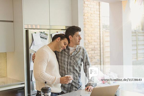 Zärtliches männliches schwules Paar mit Kaffee in der Küche