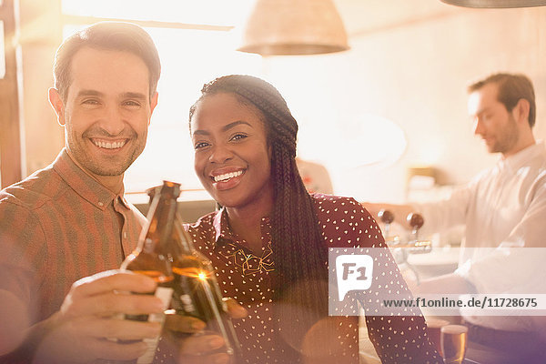 Portrait smiling couple toasting beer bottles in bar