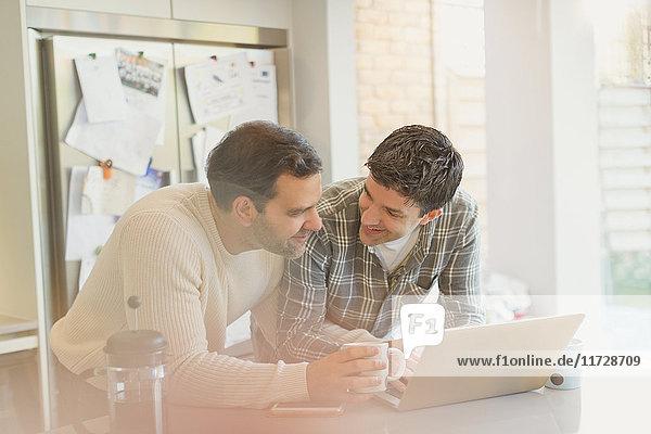 Männliches schwules Paar mit Laptop und Kaffeetrinken in der Küche