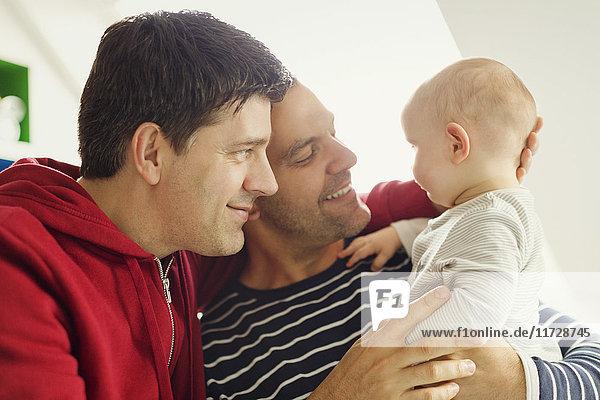Zärtliche männliche schwule Eltern kuscheln Baby-Sohn