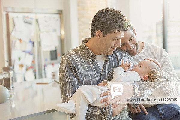 Zärtliche männliche schwule Eltern halten Baby-Sohn mit Flasche