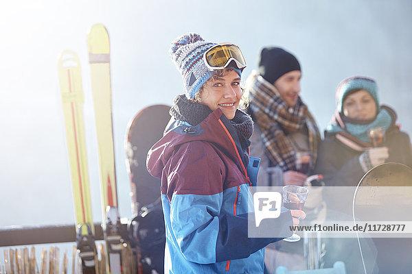 Portrait lächelnde Skifahrerin trinkt Cocktail auf dem Balkon mit Freunden Apres-Ski
