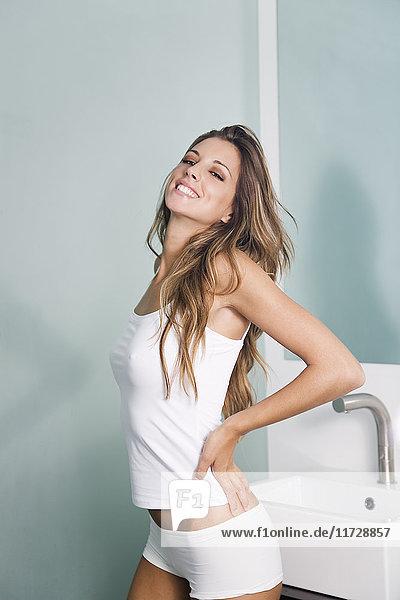 Porträt einer Frau im Bad stehend und lächelnd