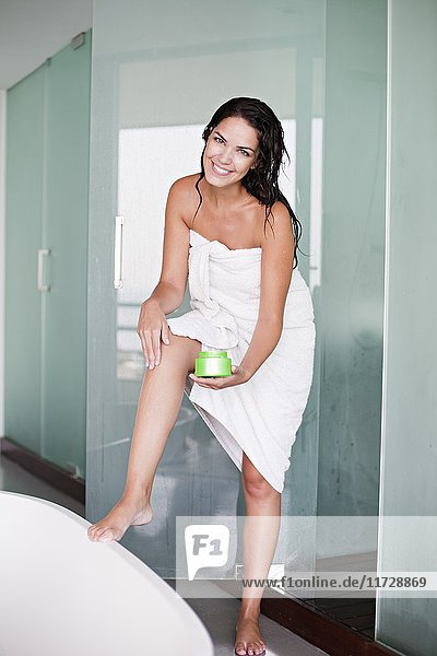 Brünette Frau  die die Feuchtigkeitspflege nach dem Duschen verbessert.
