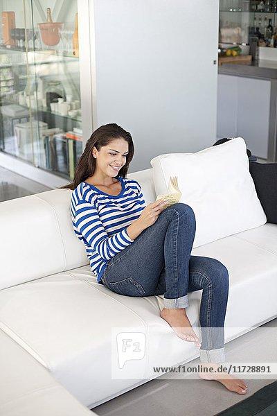 Brünette Frau beim Lesen eines Buches auf dem Sofa
