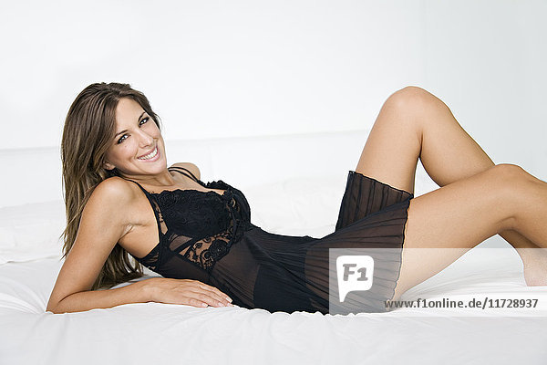 Porträt einer sinnlichen Frau im Bett lächelnd vor der Kamera