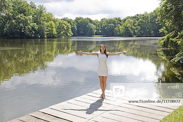 Hübsche  elegante Frau  die sich am See ausstreckt.