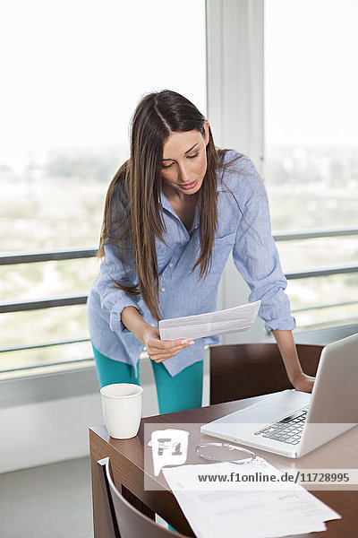 Woman reading document or bill with laptop