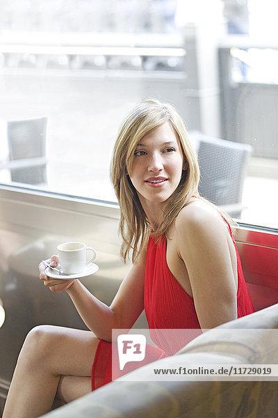 Porträt einer hübschen blonden Frau in einem Café  die jemanden ansieht.