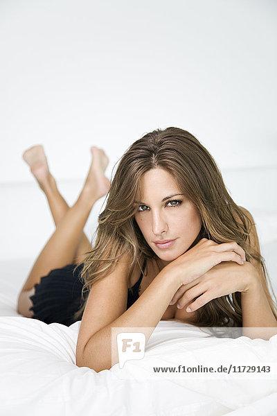 Porträt einer sexy blonden Frau im Bett mit Blick auf die Kamera