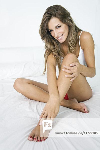 Porträt einer sinnlichen Frau auf dem Bett sitzend