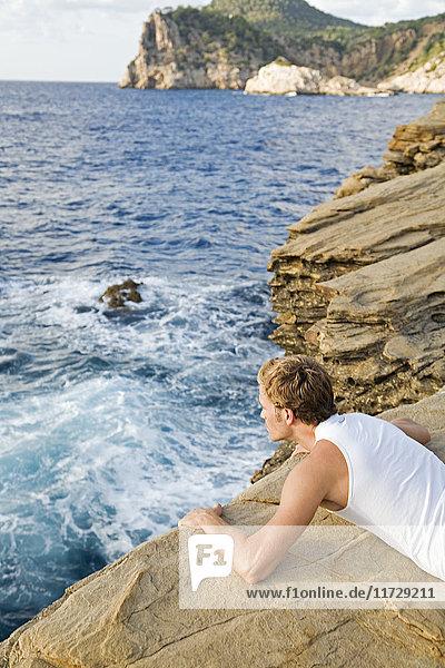 Mann blickt über die Klippe auf Ibiza