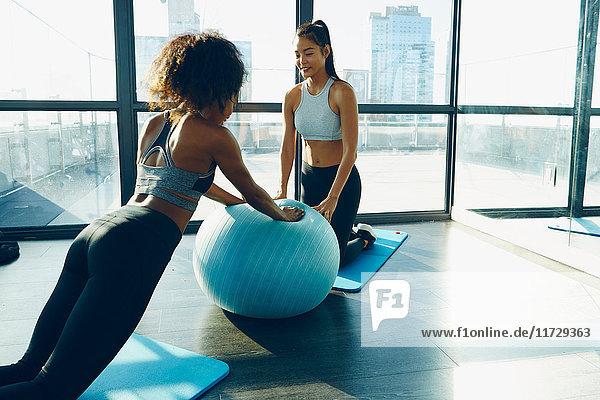 Zwei junge Frauen trainieren im Fitnessstudio mit einem aufblasbaren Übungsball