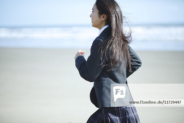 Young Japanese woman in a high school uniform running by the sea  Chiba  Japan