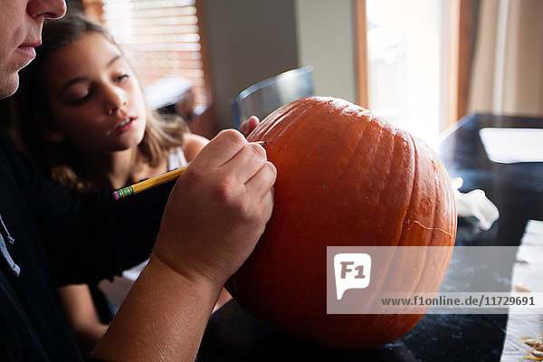 Father and daughter pumpkin carving