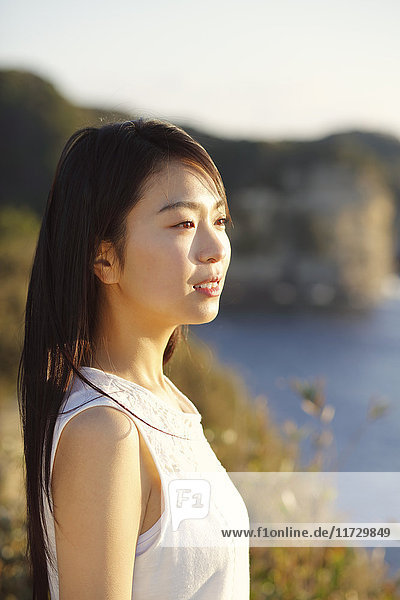Young Japanese woman in a white dress at a cliff over the sea at sunrise  Chiba  Japan