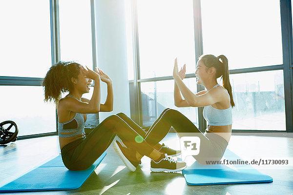 Zwei junge Frauen trainieren im Fitnessstudio und machen Sit-ups