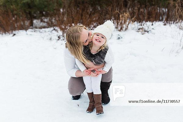 Mutter und Tochter in einem schneebedeckten Park  Oshawa  Kanada