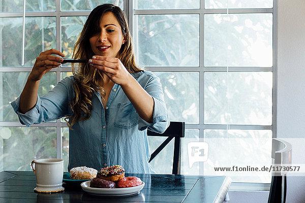 Junge Frau fotografiert Doughnut-Löcher auf dem Tisch