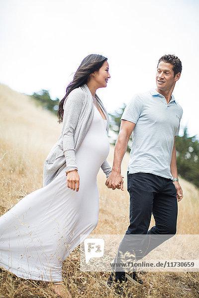 Schwangere Frau und reifer Mann  Händchen haltend  durchs Feld gehend  lächelnd