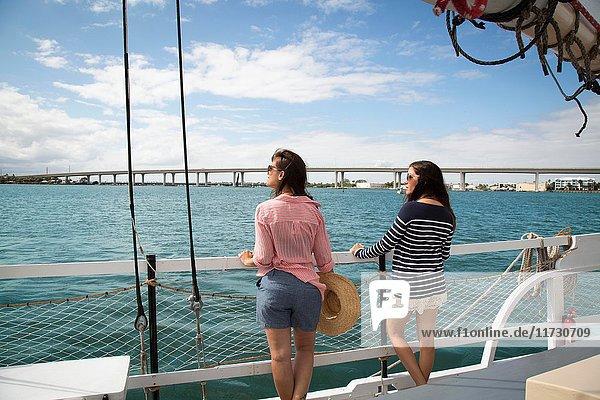 Zwei Frauen stehen an Deck eines Segelbootes  Blick nach hinten  Rückansicht