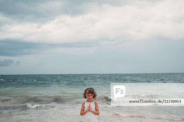 Girl praying on beach  Cancun  Mexico