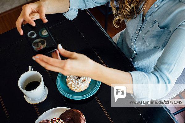 Draufsicht einer Frau  die ein Doughnut-Loch und Kaffee auf dem Tisch fotografiert
