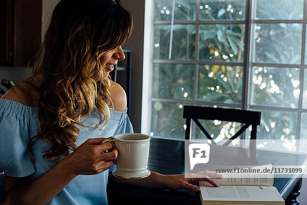 Junge Frau liest Buch bei Tisch