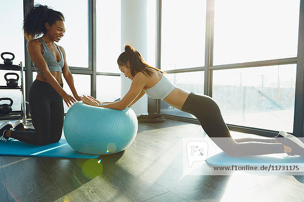 Two young women exercising in gym  using inflatable exercise ball