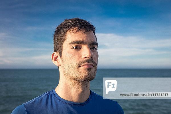 Porträt eines jungen Mannes im Freien  am Wasser  wegschauend