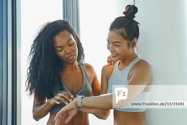 Zwei junge Frauen im Fitnessstudio mit Blick auf den Aktivitätsverfolger