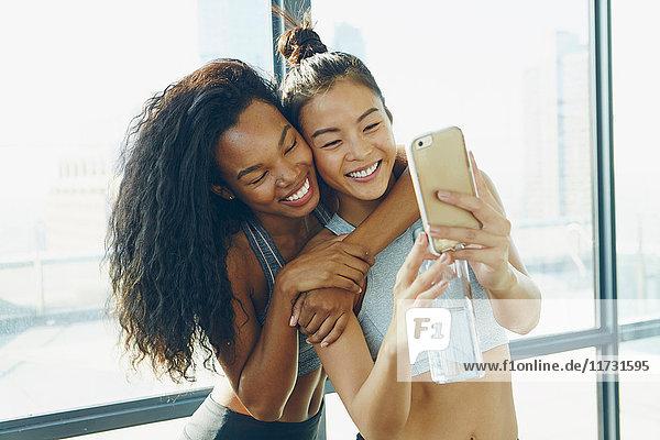 Zwei junge Frauen im Fitnessstudio  beim Selfie  mit Smartphone