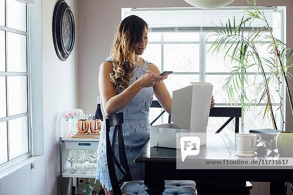 Junge Frau fotografiert geöffnete Kuchenschachtel auf dem Tisch