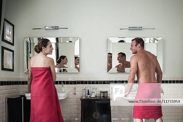Junges Paar am Waschbecken in seinem und ihrem Badezimmer