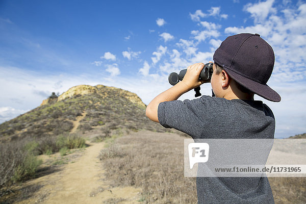 Boy looking through binoculars at landscape  Thousand Oaks  California USA