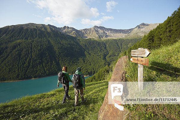 Rear view of young couple hiking at Vernagt reservoir  Val Senales  South Tyrol  Italy
