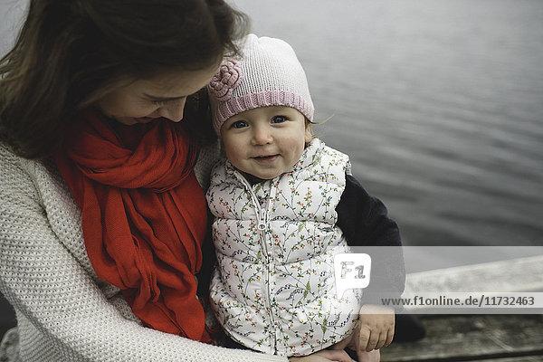 Mutter und Tochter sitzen zusammen auf dem Steg