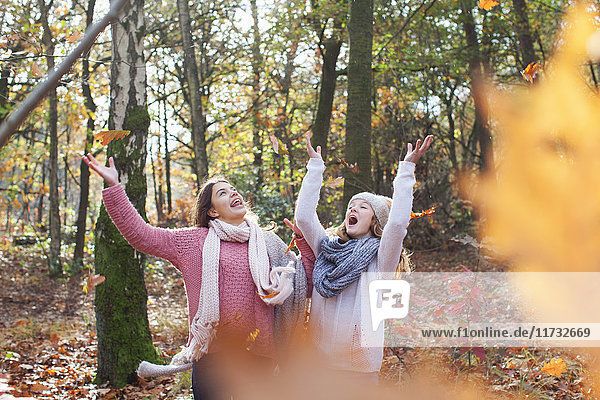 Teenage girls in forest arms raised throwing autumn leaves smiling