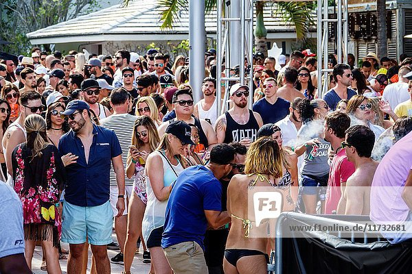 Florida  Miami Beach  Miami Music Week  hotel pool party  crowd  standing  dancing  drinking  young adult  men  women