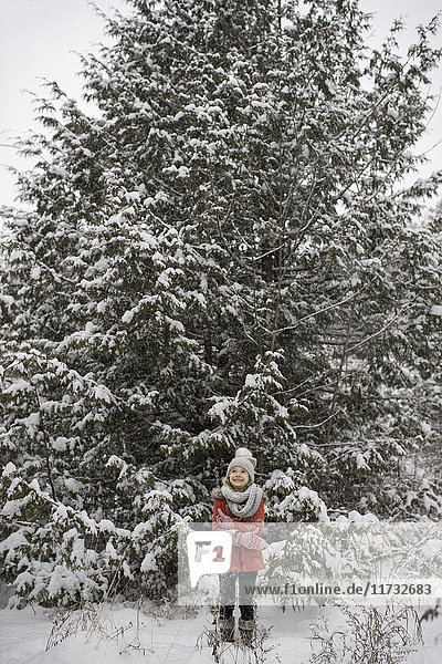 Young girl standing in front of large evergreen tree  covered in snow
