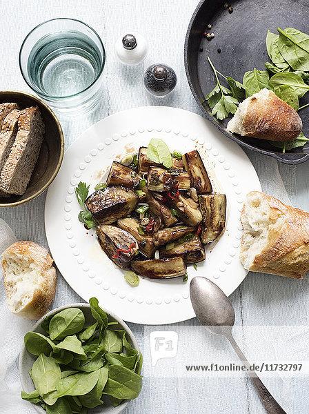 Stilleben eines Tellers mit gebratenen Auberginen mit Garnierung und Spinat