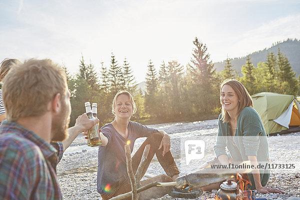 Erwachsene  die am Lagerfeuer sitzen und mit Bierflaschen anstoßen