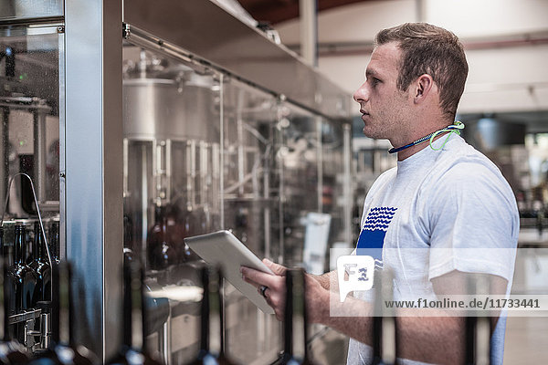 Young man working on production line with digital tablet in bottling plant