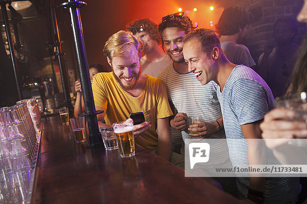Group of friends smiling at smartphone in club