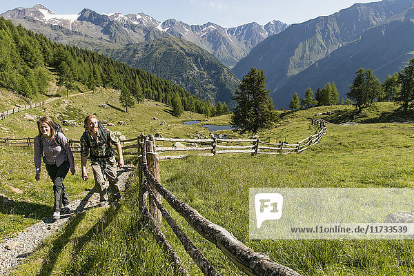 Young hiking couple up path  Karthaus  Val Senales  South Tyrol  Italy