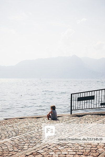 Rear view of boy sitting cobbled steps looking out at view  Luino  Lombardy  Italy