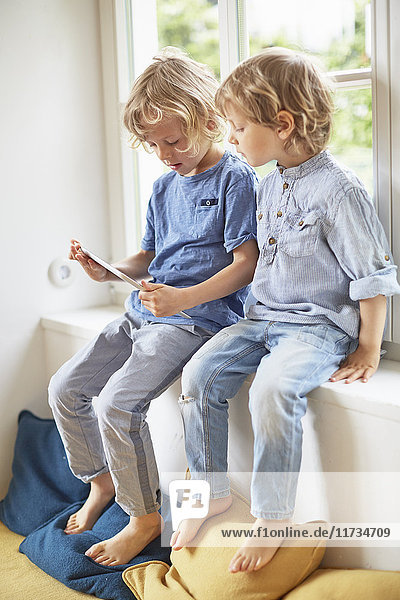 Two young brothers  sitting in window seat  looking at digital tablet